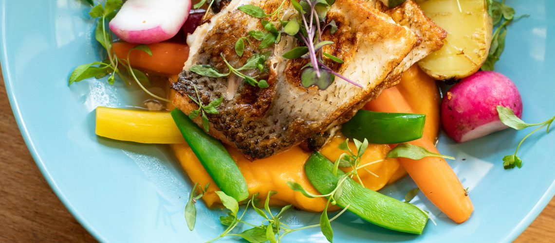 fried-fish-with-vegetables-dish-on-teal-plate-1516415